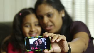 mom and daughter taking a selfie focus on phone