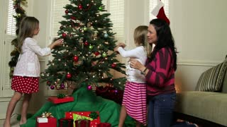 Mom helping kids decorating Christmas tree