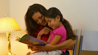 Mom reading a book to her young daughter 4K.