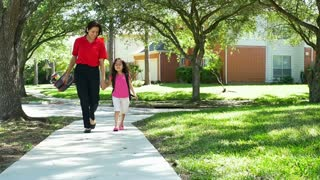 mom walking her little girl home from school slow motion.