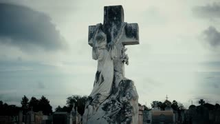 monument of woman hanging on a cross in Metairie Cemetery New Orleans