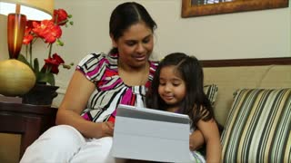 mother and daughter using a tablet smile at camera