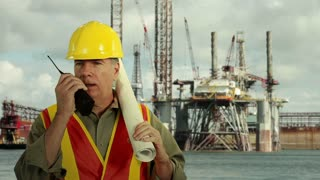 Oil platform worker with plans