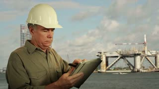 Oilfield worker on phone and using a tablet pc.