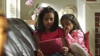 Older sibling sings along with what she and little sister see on tablet pc
