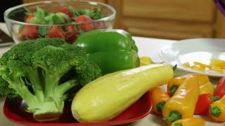 pan to woman cutting yellow pepper.