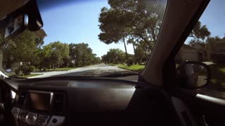 POV fisheye view from inside a car driving through a typical suburban street 4k