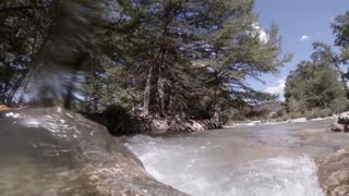 pov view of a person rafting through fast water in a river