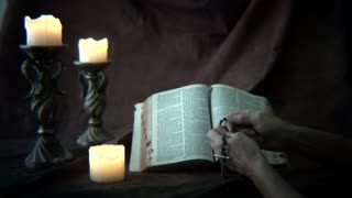 praying the rosary with bible and candles