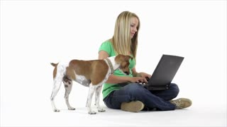 Pretty girl on laptop and playing with her dog