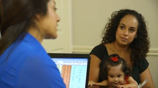 pretty Hispanic mom smiles when young son gives hi-five to  administrator