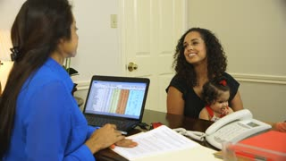 Pretty Hispanic mom with baby talking to businesswoman in office