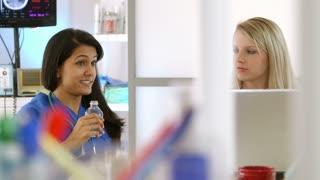 pretty smiling nurses talk to someone off scene