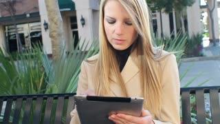 Pretty young businesswoman with tablet smiles at camera