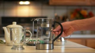 putting coffee grinds in the french press slow motion.