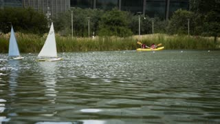 radio controlled sailboats and kyackers in a urban parks pond 4k