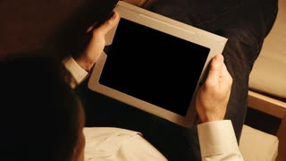 Relaxing man looking at a tablet pc with alpha