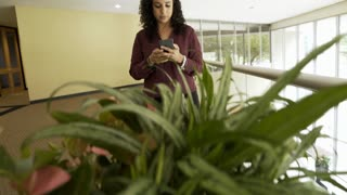 reveal businesswoman texting on her cell phone in the office and walks off 4k