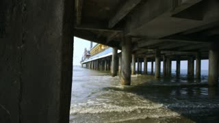 reveal from behind pier to under a large wharf