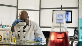 scientist looking in microscope and making notes 4k