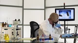 scientist moves from laptop to microscope 4k