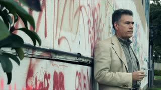 Serious man in front of grafitti wall