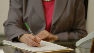shallow DOF of businesswoman signing a legal document