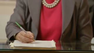 shallow DOF of businesswoman writing on a document