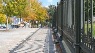 Sidewalk next to decorative wrought iron fence 4k.