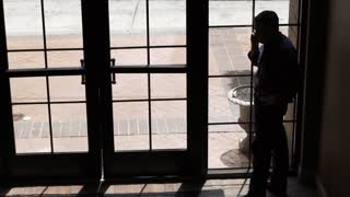silhouetted businessman on a cell phone next to a window 4k