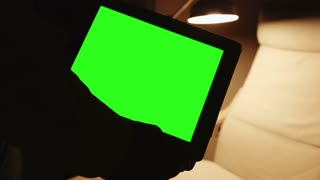 silhouetted tablet pc with cozy reading place in background with green screen