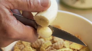 slow motion cutting a banana in breakfast cereal