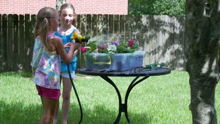 slow motion little girl squirting her sister with the garden hose.