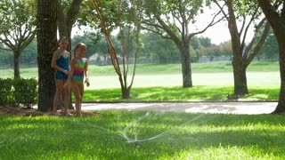 slow motion little girls jumping over a water sprinkler