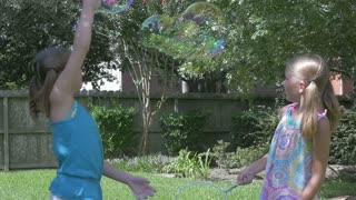 slow motion little girls playing with bubbles.