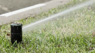 slow motion pop up lawn sprinkler in the grass