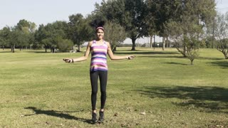 slow motion walking to a young woman jumping rope in a park
