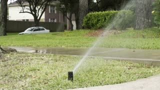 slow motion wide shot of lawn sprinkler in a neighborhood yard