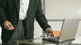 Standing businessman typing on laptop