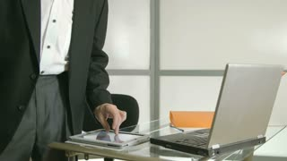 standing businessman working on tablet pc