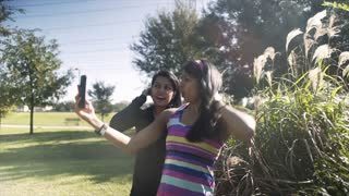 steadicam shot of twin sisters taking selfies in a park 4k
