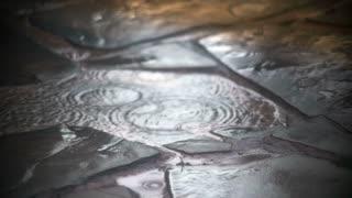 Summer rain on a slate walkway slow motion