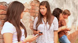 teen girls talking next to a brick wall