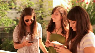 teen girls texting outdoors