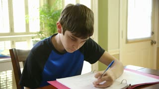 teenage boy doing homework smiles at camera