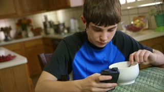 teenage boy eating listens to music on smart phone.