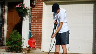 teenage boy making extra money power washing driveway