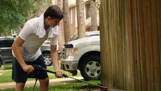 teenage boy power washing old fence