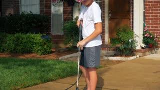 Teenage boy powerwashing a dirty driveway