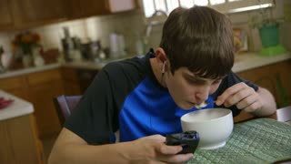 teenage boy uses smart phone while eating cereal.